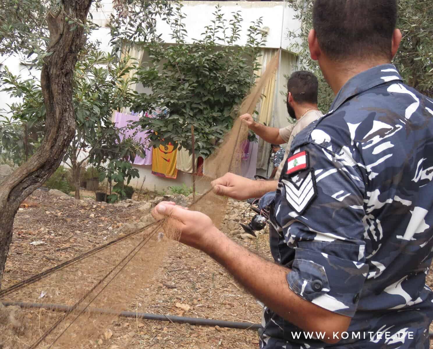Funkcjonariusze zdejmują sieci do chwytania ptaków